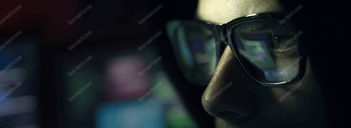 hacker with glasses in the dark