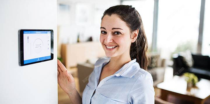 woman looking at tablet with smart home screen