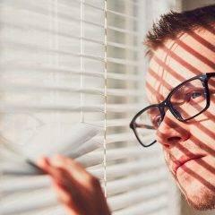 curious man looking through a jalousie