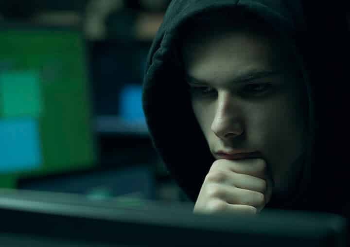 hacker with hoodie working with computers