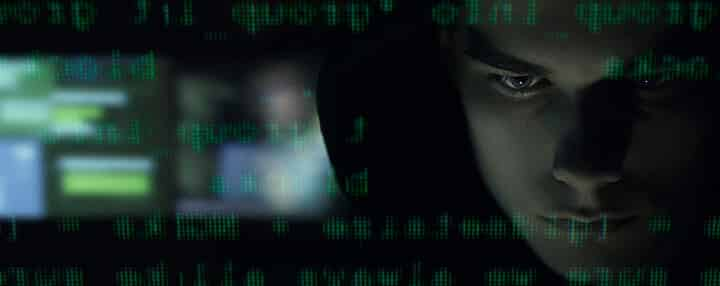 person in the dark looking at a computer